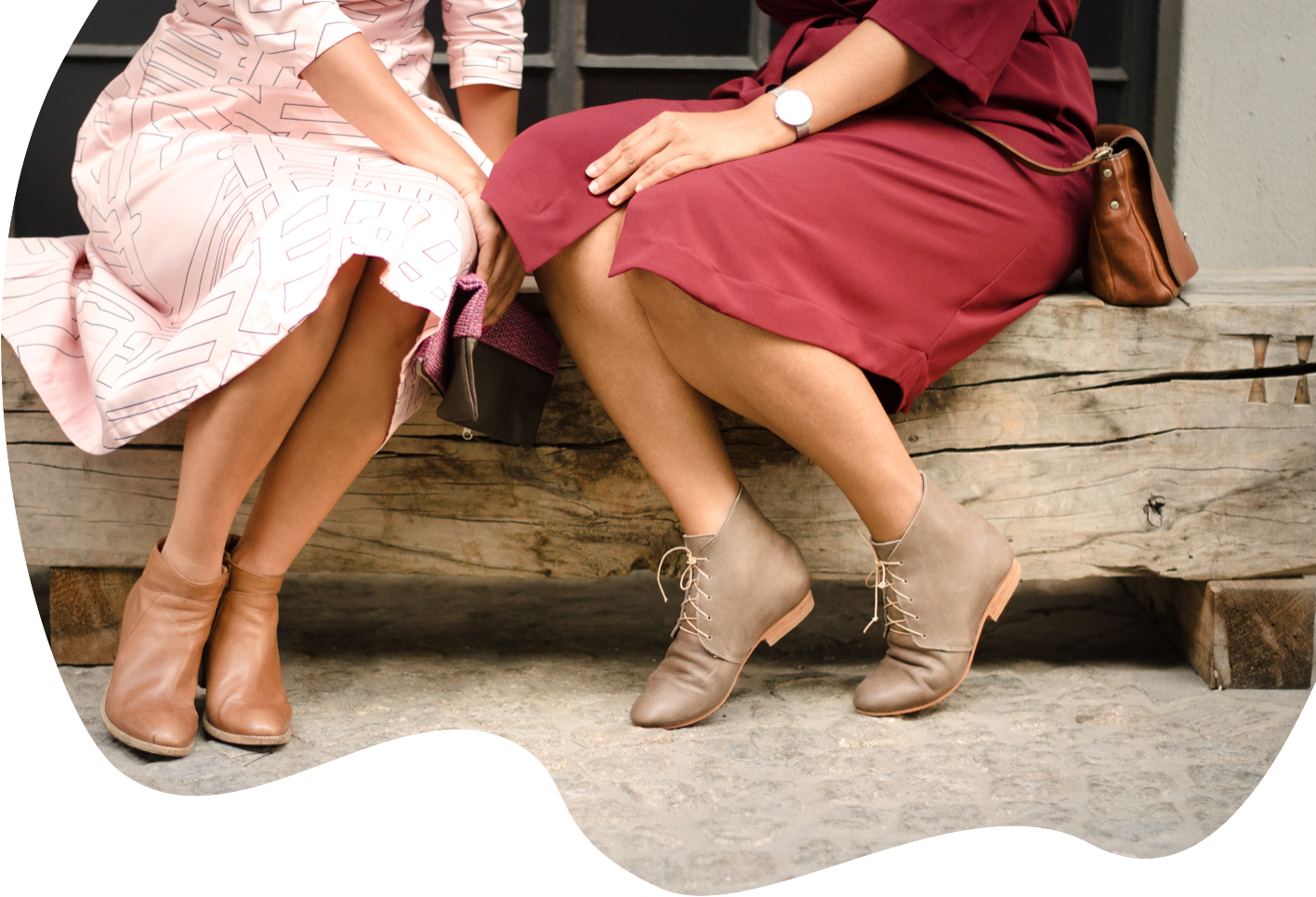 Waist down of two women sitting on wooden log touching knes wearing dresses
